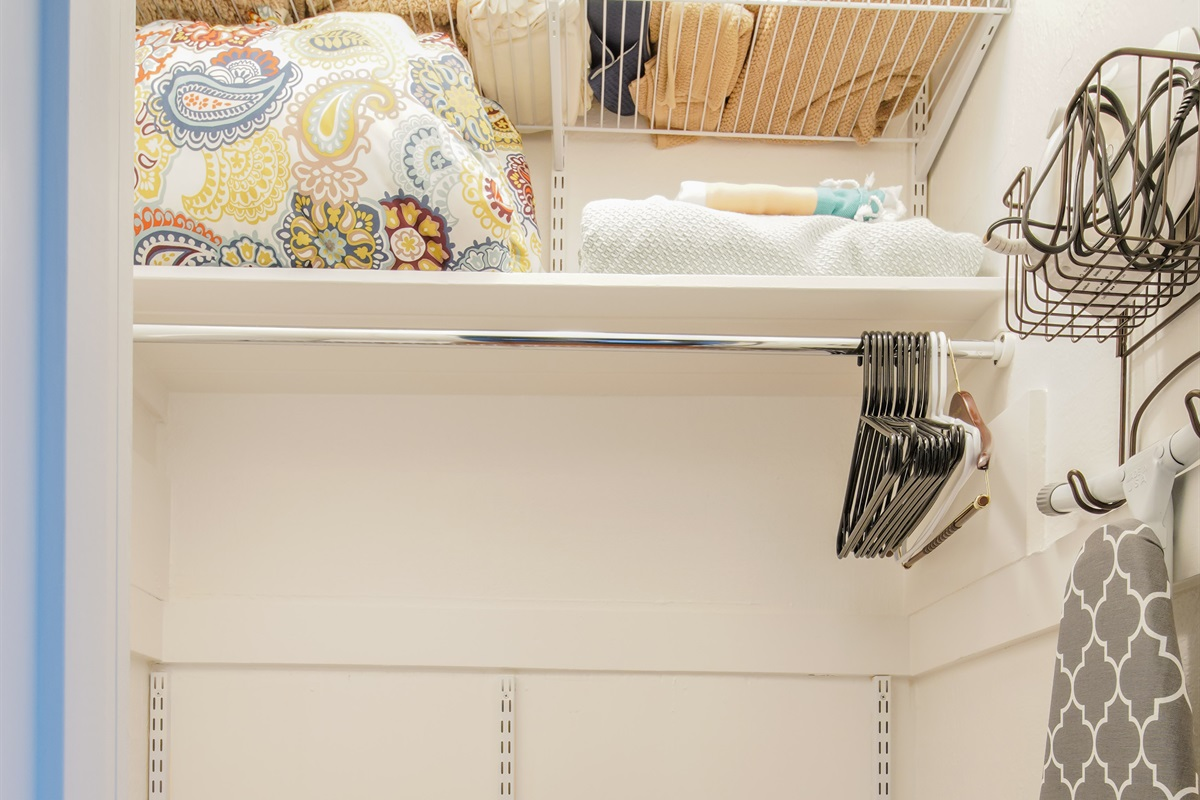 Roomy, tall, lighted closet, with shelves, drawers, iron and ironing board.
