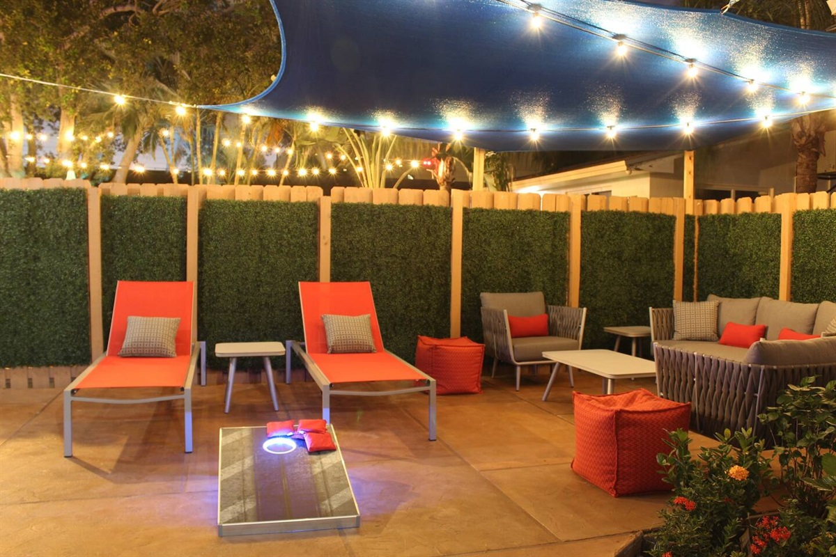 Lounge or picnic in your own patio surrounded by a warm stained wood fence, wrapped in artificial boxwood greenery for complete privacy. The blue sail above provides some shade from the sun without blocking it and helps create cabana vibes. :-)