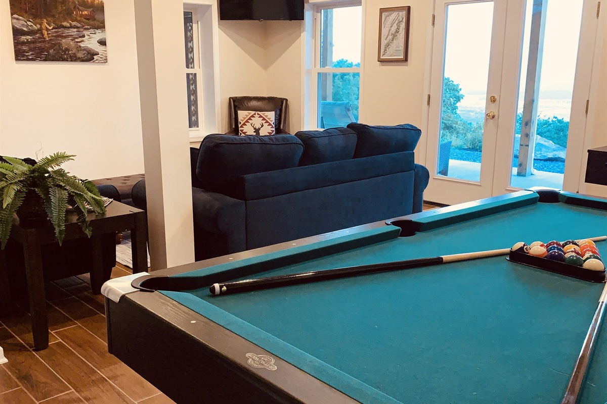 Game room on first floor with pool table and foosball