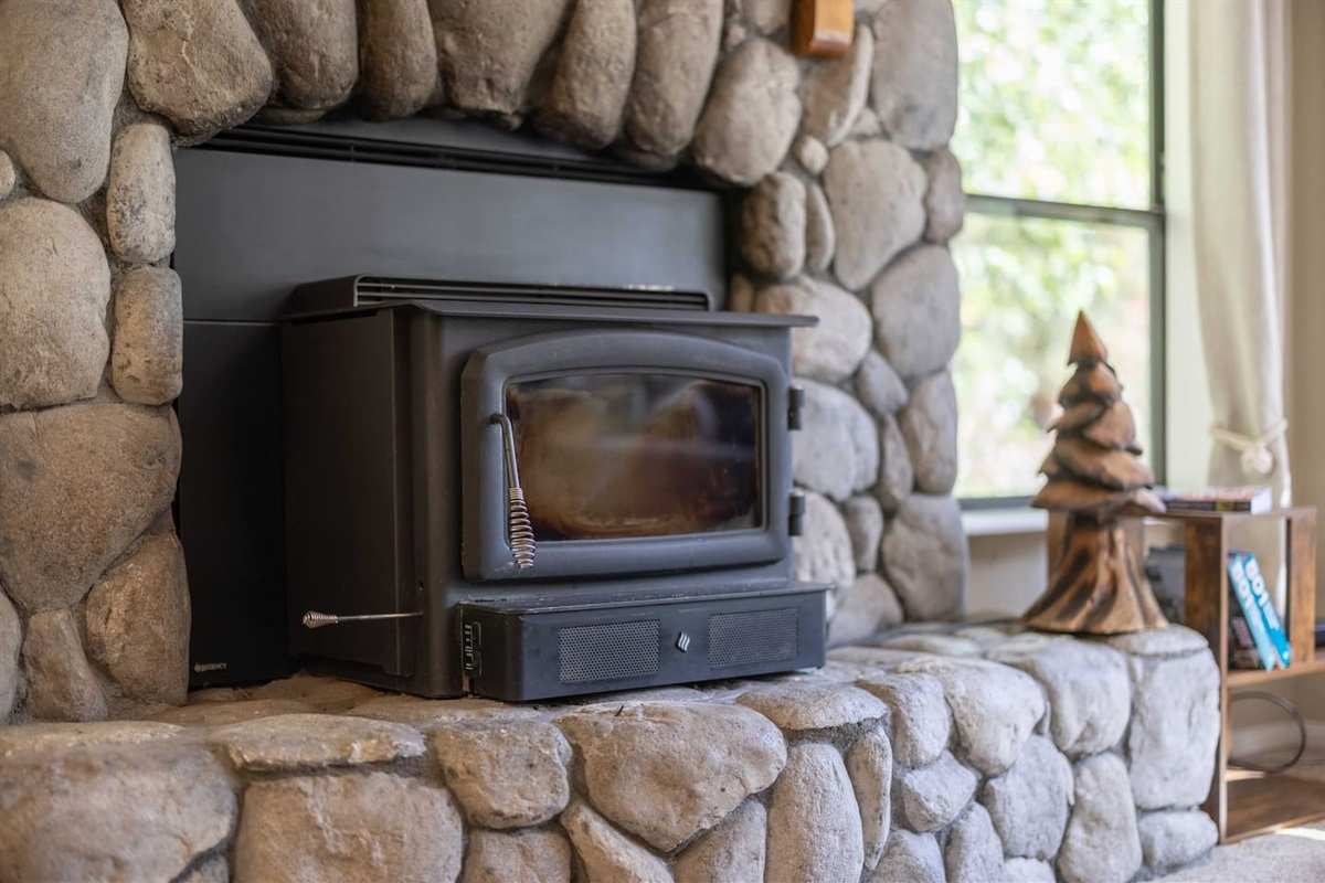 The wood burning fireplace is framed by beautiful natural stone.