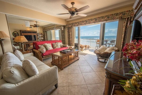Living Room with large screen TV and balcony to oceanfront pool and beach