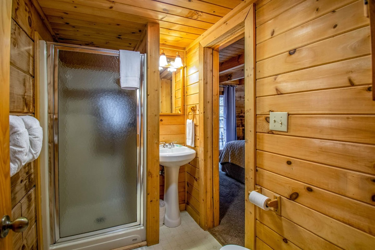The main level bathroom has a stall shower and is shared with the living area.