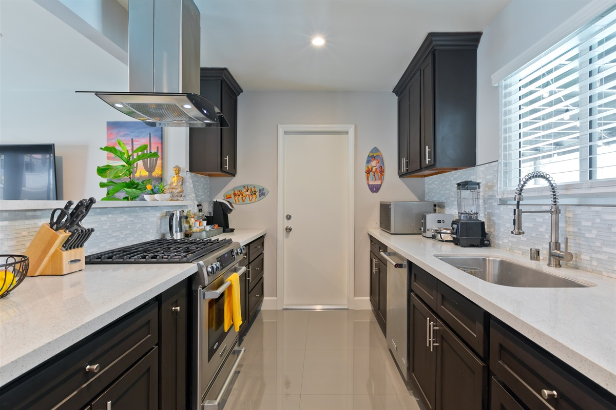 The kitchen is equipped with stainless steel appliances, including a gas stove, brand new microwave, Ninja professional blender, toaster, and Belgian waffle-maker