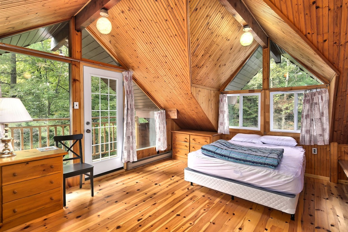 Sprawl out in your very own loft style wood bedroom with high vaulted ceilings and a walkout balcony over looking the woods...We often have deers running around in the backyard!