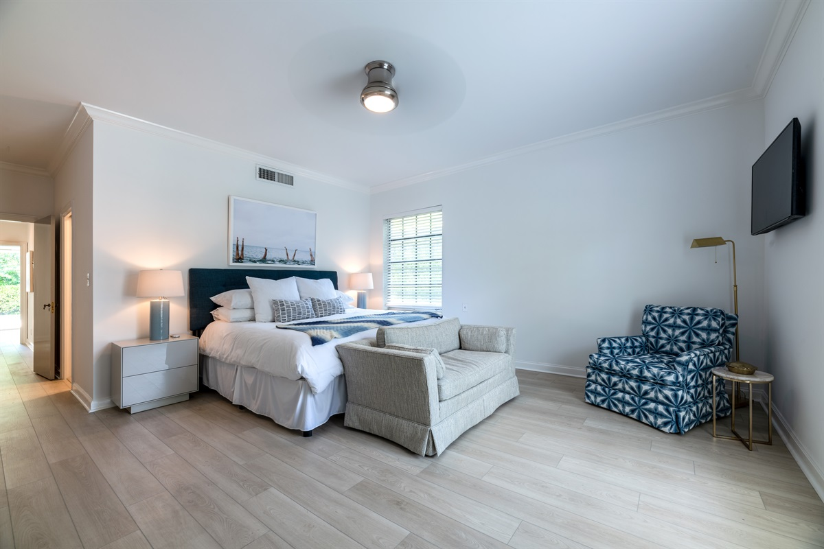 Stunning spacious Master Bedroom with King sized bed, Smart App TV and gold light, cute loveseat at the foot of the bed, stunning armchair in the corner under the SMART TV.