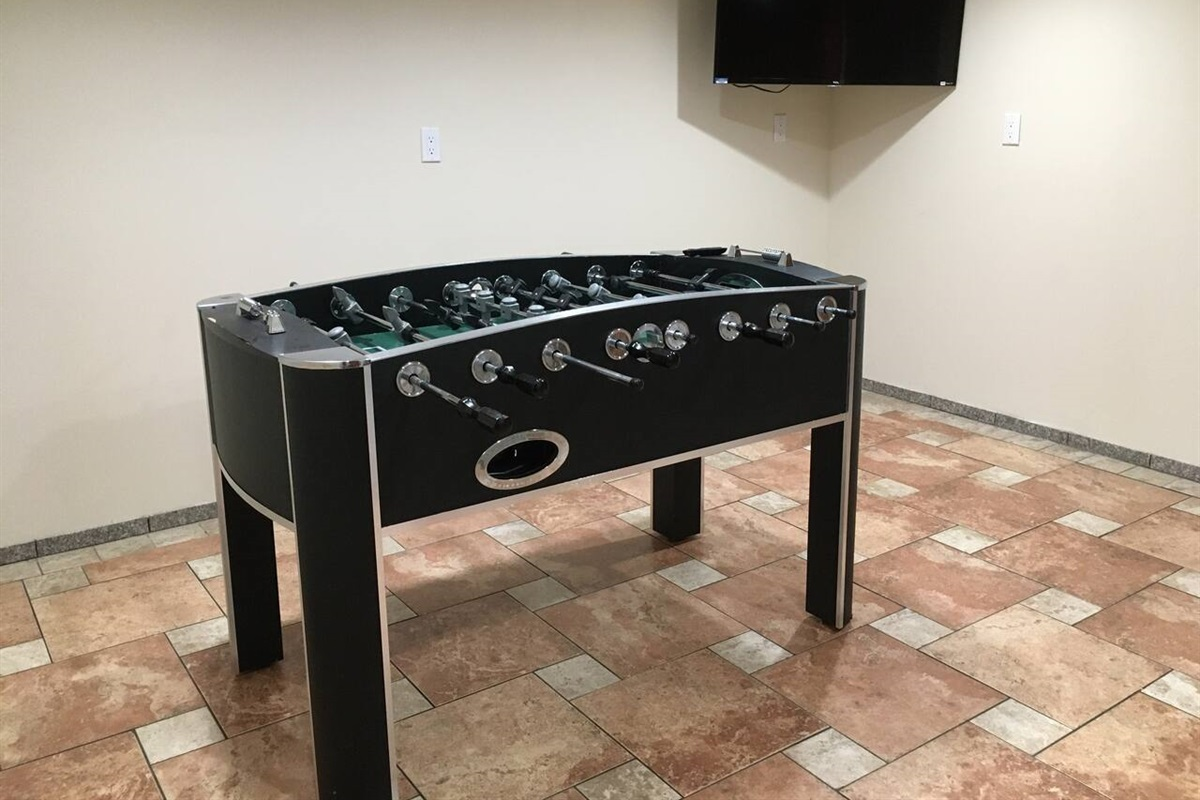Foosball table and smart Roku TV in basement game room/laundry