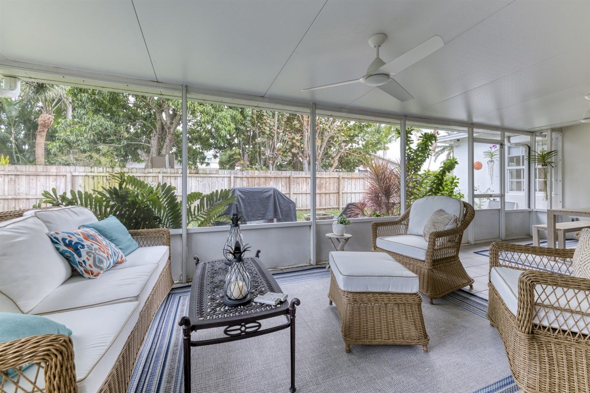 Enjoy Florida's stunning climate outdoors. Comfortable wicker furniture & outdoor dining bench. BBQ and outdoor loungers.