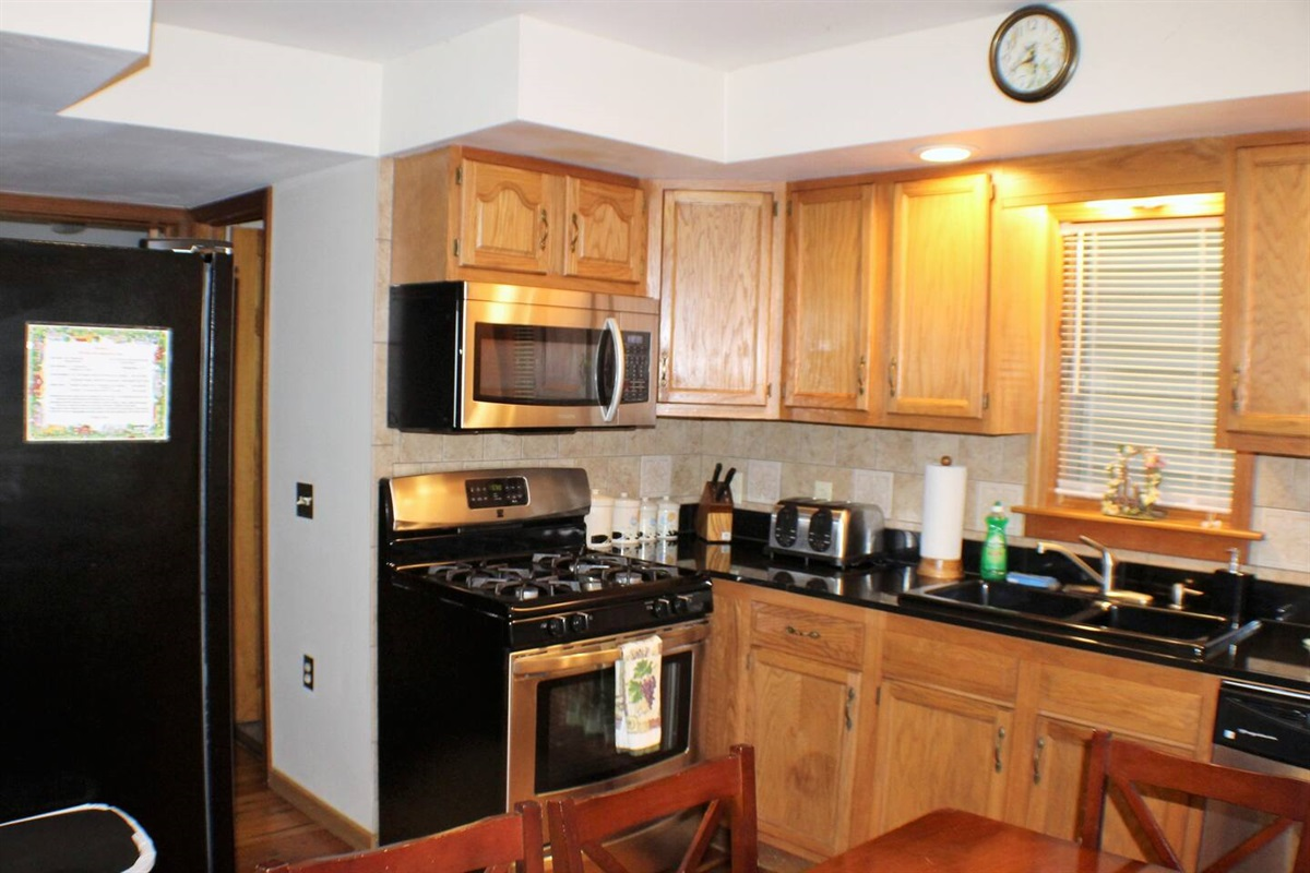 Kitchen with stainless steel gas range, microwave and dishwasher