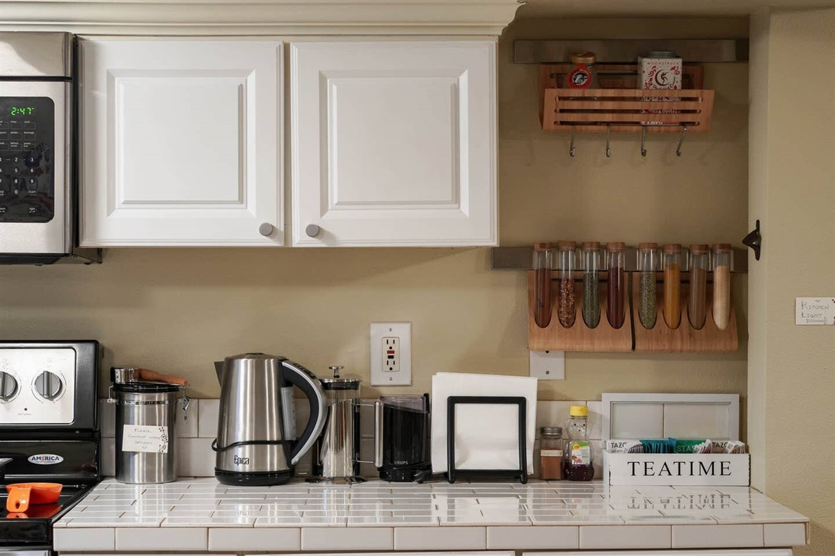 The kitchen is well stocked with teas, herbs, condiments, and creamers.