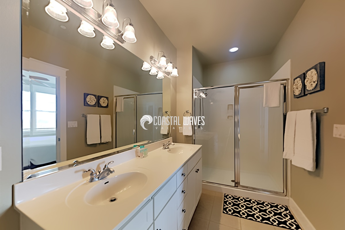 Ensuite bath with double vanity sinks and shower