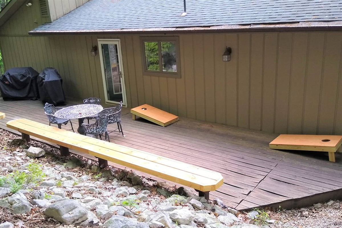 Back patio - 2 propane gas grills, cornhole boards, metal dining table and chairs, built-in benches. the front patio has 2 picnic tables, and a kid size picnic table.