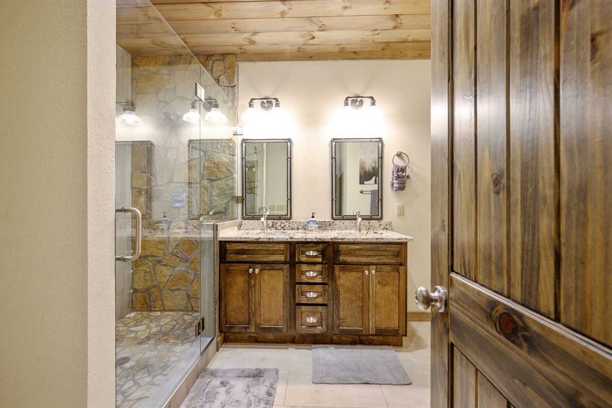 Downstairs second master bath features a double vanity and roomy shower area