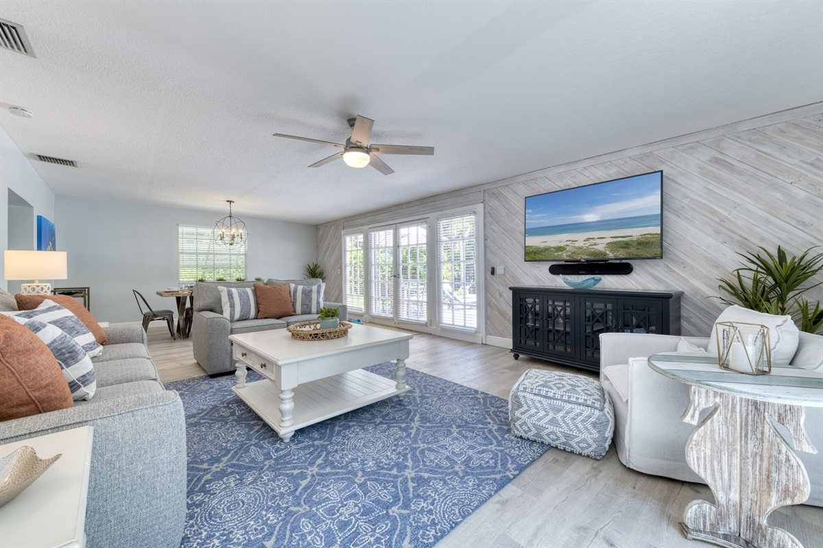 """Exquisitely decorated second living room with huge 64"""" Smart TV, pull out Queen TempurPedic sofa and views of the sunny outdoors."""