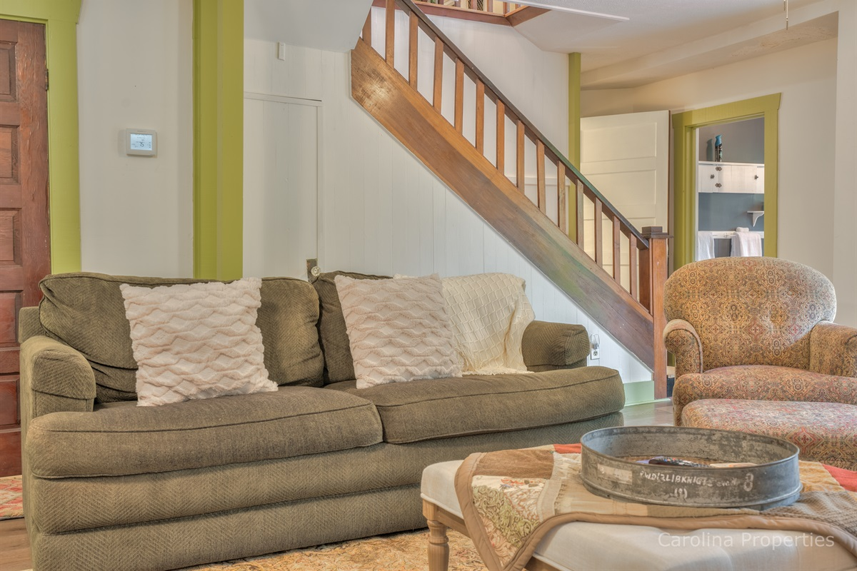 Lower level living room with comfortable seating and stairs