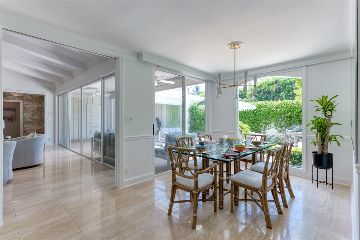 Dining is absolute luxury, large panaramic view windows and large mirror with reflections of the outdoor space. rustic dining chairs, tasteful dining room table and low hanging white & gold light fixture.
