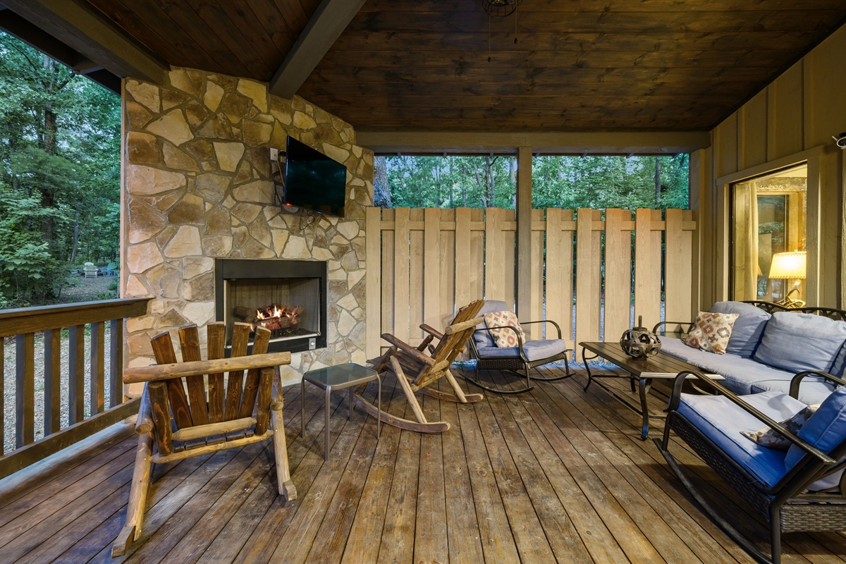 Private back sitting area with plenty of seating, gas fireplace and smart TV
