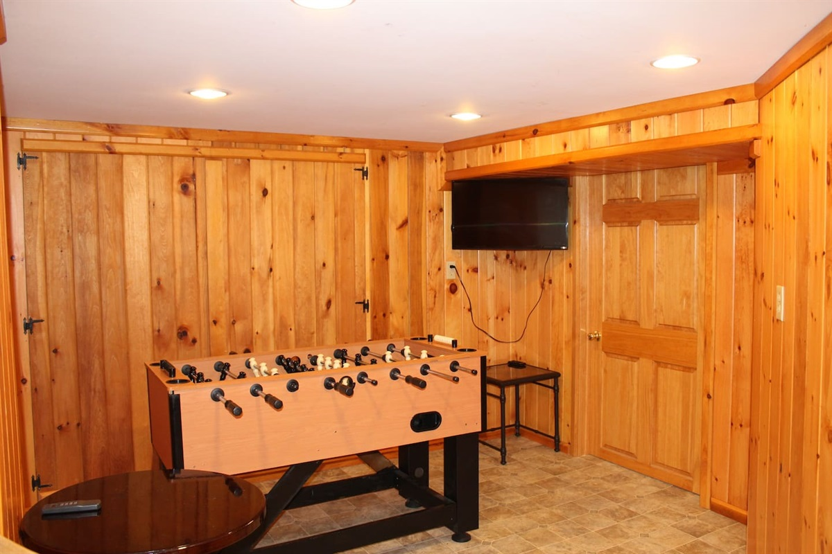 Game room downstairs with foosball table and a flat screen smart Roku TV