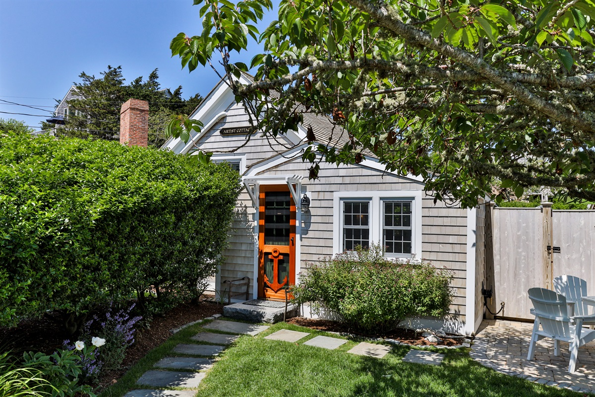 A tall holly hedge separates the Artist Cottage from the Captain's House backyard and provides privacy for guests. Two double hung windows from the first floor bedroom look out into the fro