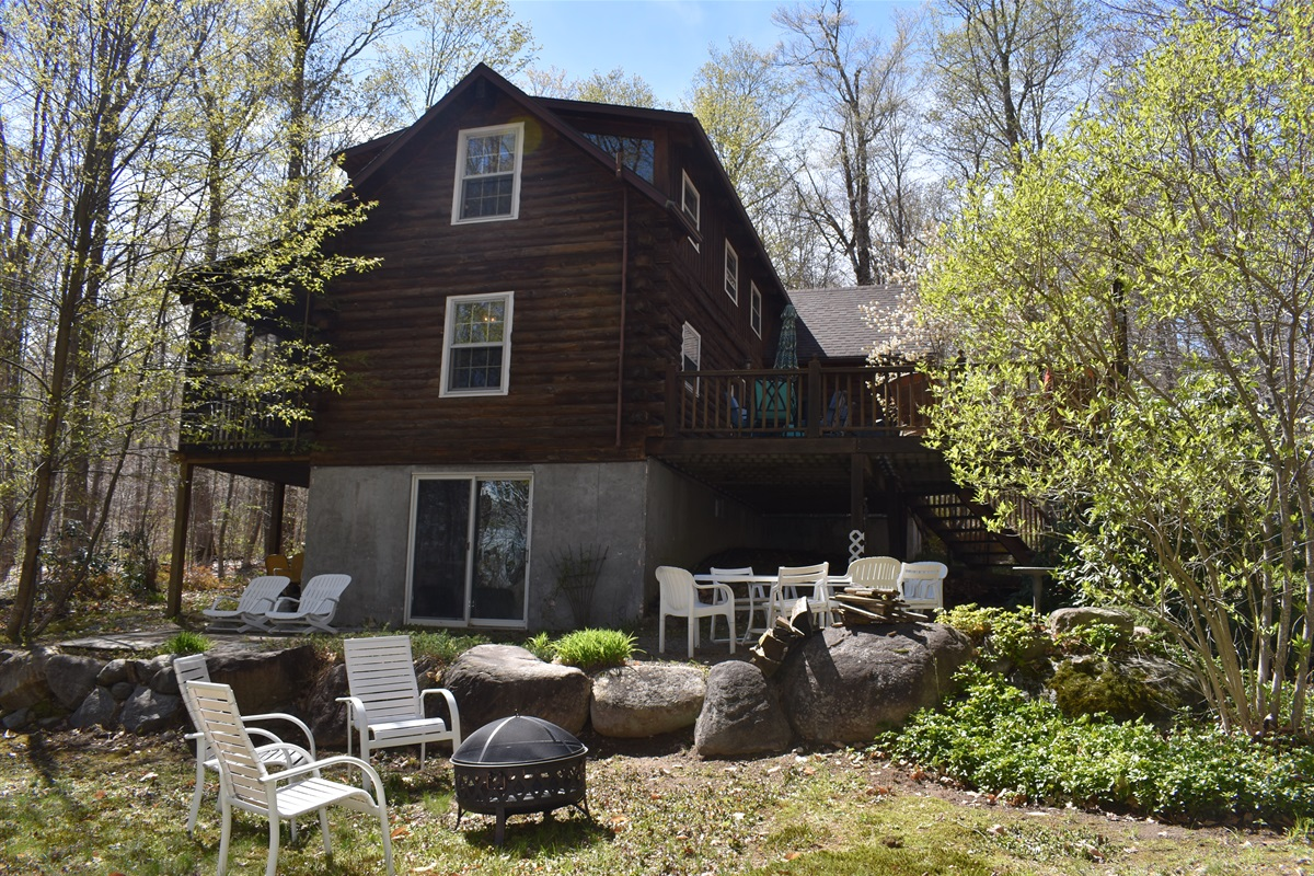 Back deck overlooks fire pit, yard and seating areas