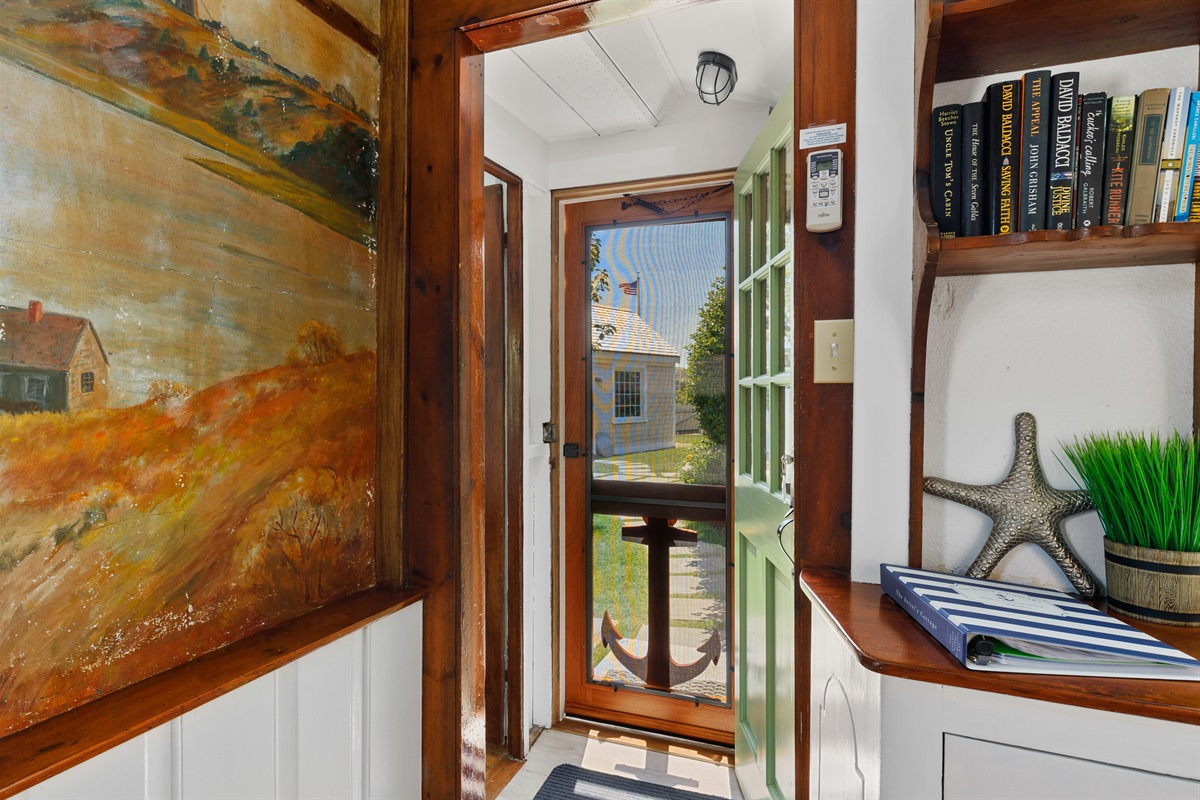 The front entry steps into a small alcove with the 1st floor master bedroom located to the immediate right and a storage closet to your left. One step up brings you into the main A-frame portion of the cottage with the living room & kitchenette.