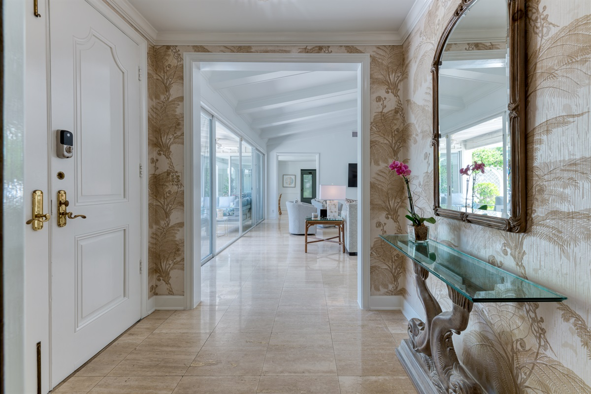 Beautiful entrance with large mirror and unique wallpaper makes you feel welcome to this warm family home.