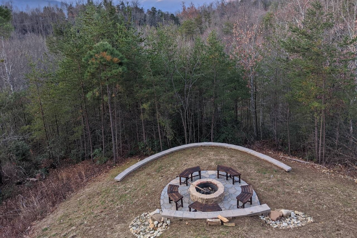 New landscaping with wooden outdoor furniture around the fire pit and space to play on the lawn