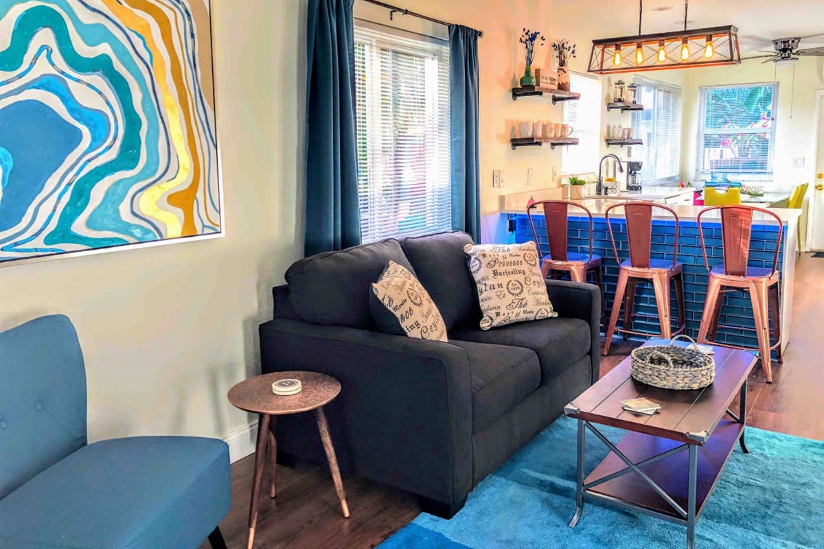 You'll enter the living room from the den. This communal space can seat up to 8 people = 3 on the copper chairs at the bar, 2 on the love seat, one in the turquoise accent chair and two on the two gray ottomans located under the TV console.