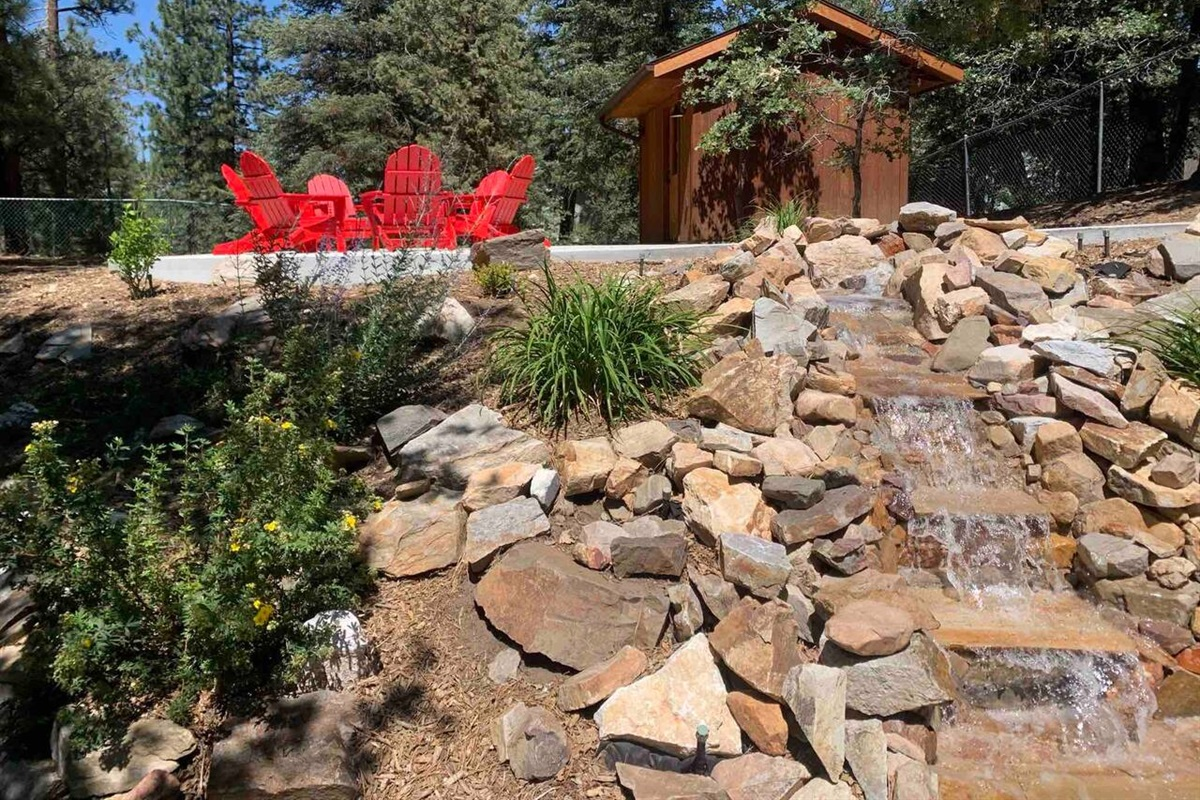 Relax in the backyard, with the babbling brook water feature and new adirondack chairs.