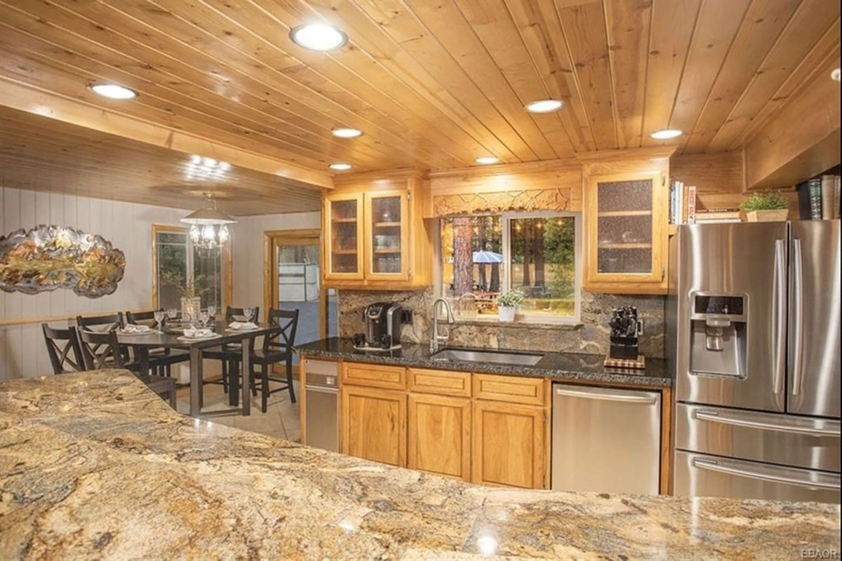 Kitchen: A fully stocked kitchen with stainless steel appliances, island with breakfast bar, and gourmet flair.