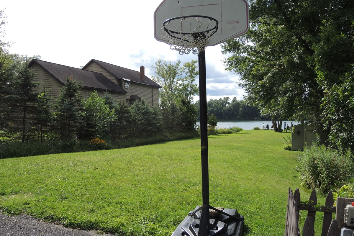 Basketball hoop and lawn leading to water