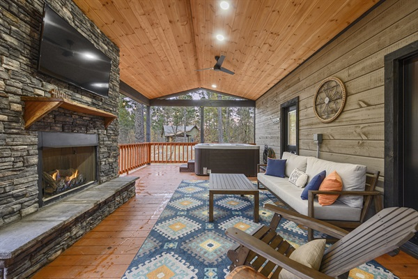 East facing covered back patio, stacked rock firepace, hot tube and seating