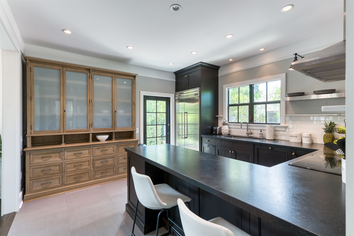 State of the Art kitchen with a unique black counter and non-slip flooring. The kitchen is a cooks dream. Loads of closet space and preparation areas. Two bar stools stand on the other side for additonal dining seating. Stainless Steel appliances.