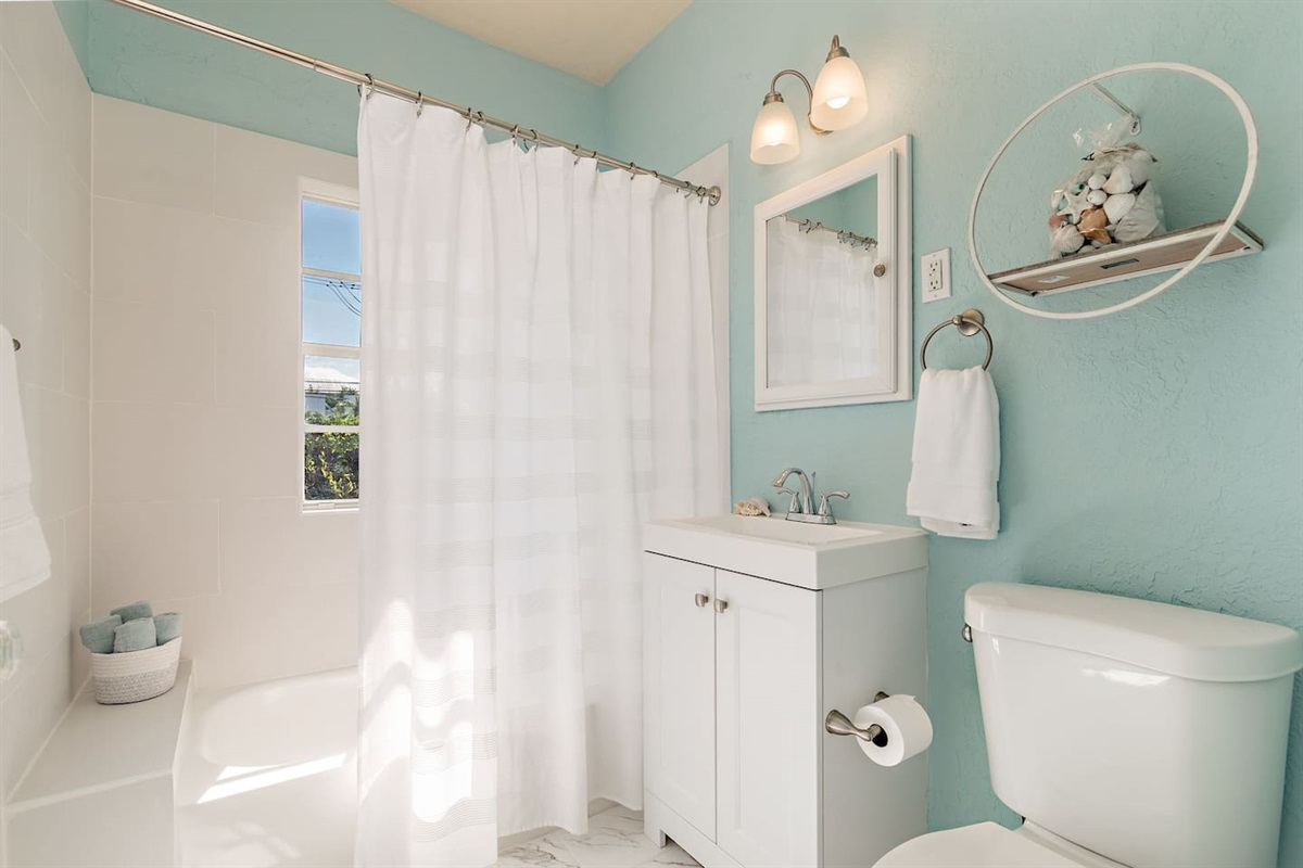 The bathroom is shared between both bedrooms. There is a combination Tub/ Shower. Beachy theme with soft blues and whites.