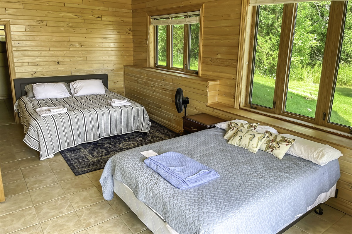 Bedroom 6 (lower level) with a king and queen bed. Access to backyard and incredible views of the lake and surrounding greenery.
