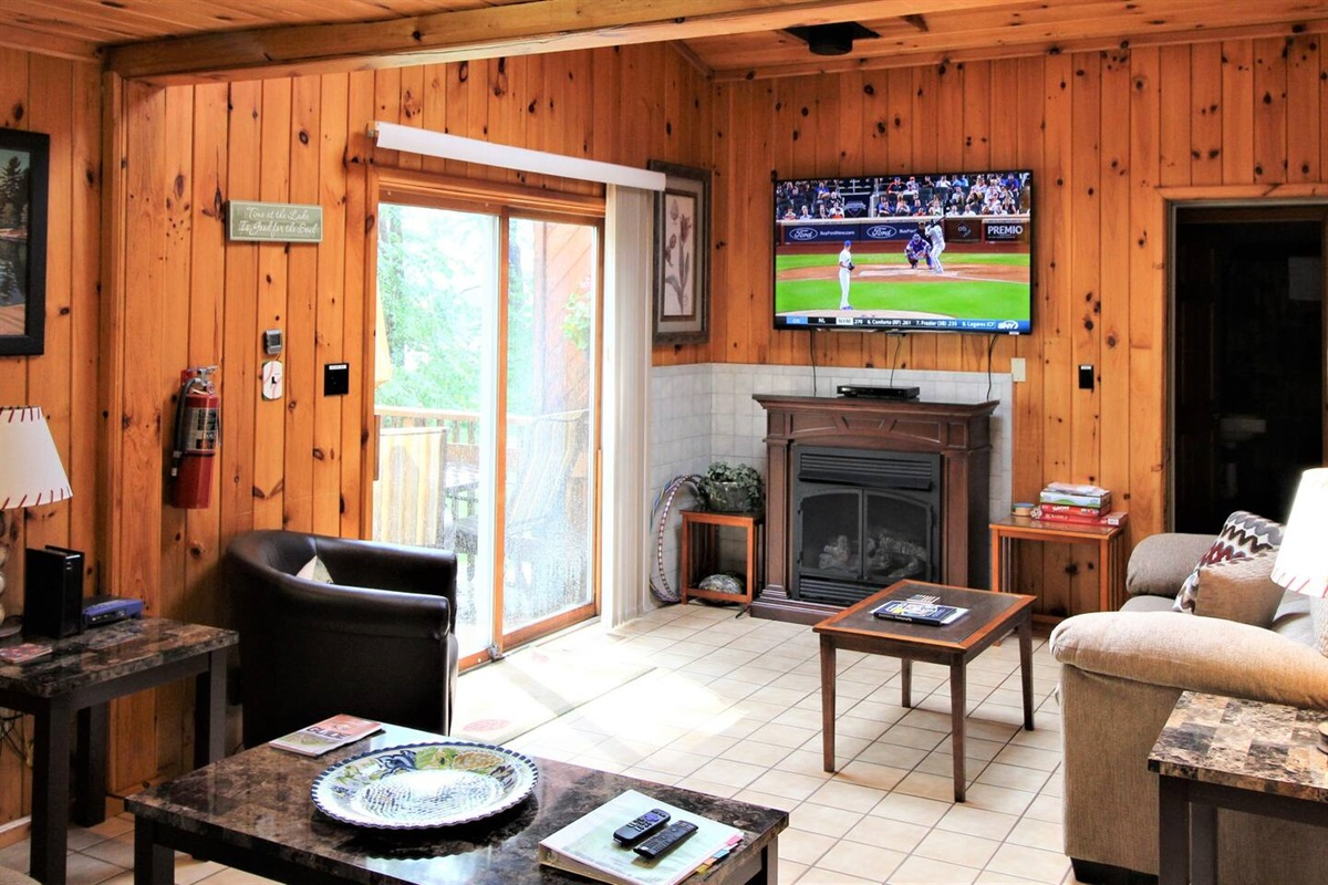 """Living room with 55"""" (or larger) flat screen smart TV with Roku.  Bring your favorite streaming apps to never miss the action of your favorite team!"""