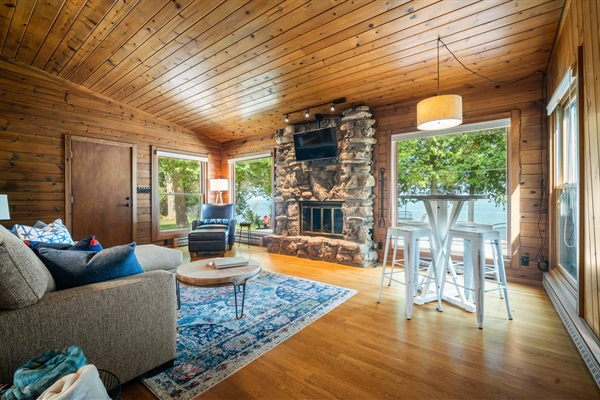 The living room features a couch, reading chair, game table and fireplace.