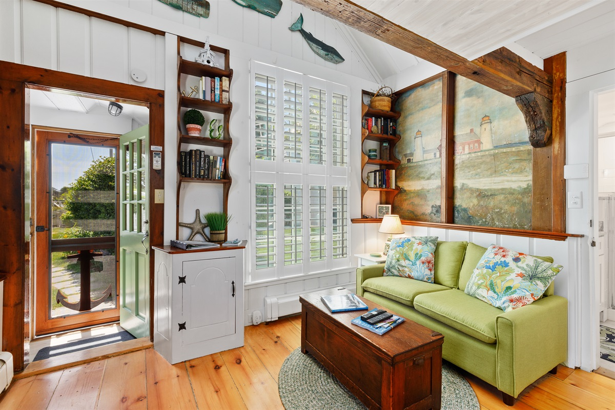 Bright and sunny sitting room with full bathroom to the right. Large window with privacy shutter in the living room surrounded by original built-ins with many classic maritime novels & coastal decor to create a warm & inviting space for our guests.