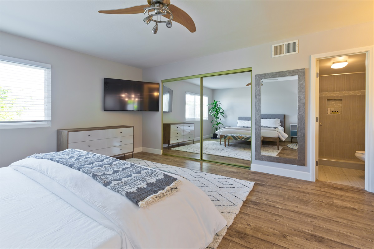 Spacious master bedroom with full-length mirrors, a private bath, and isolated vanity.
