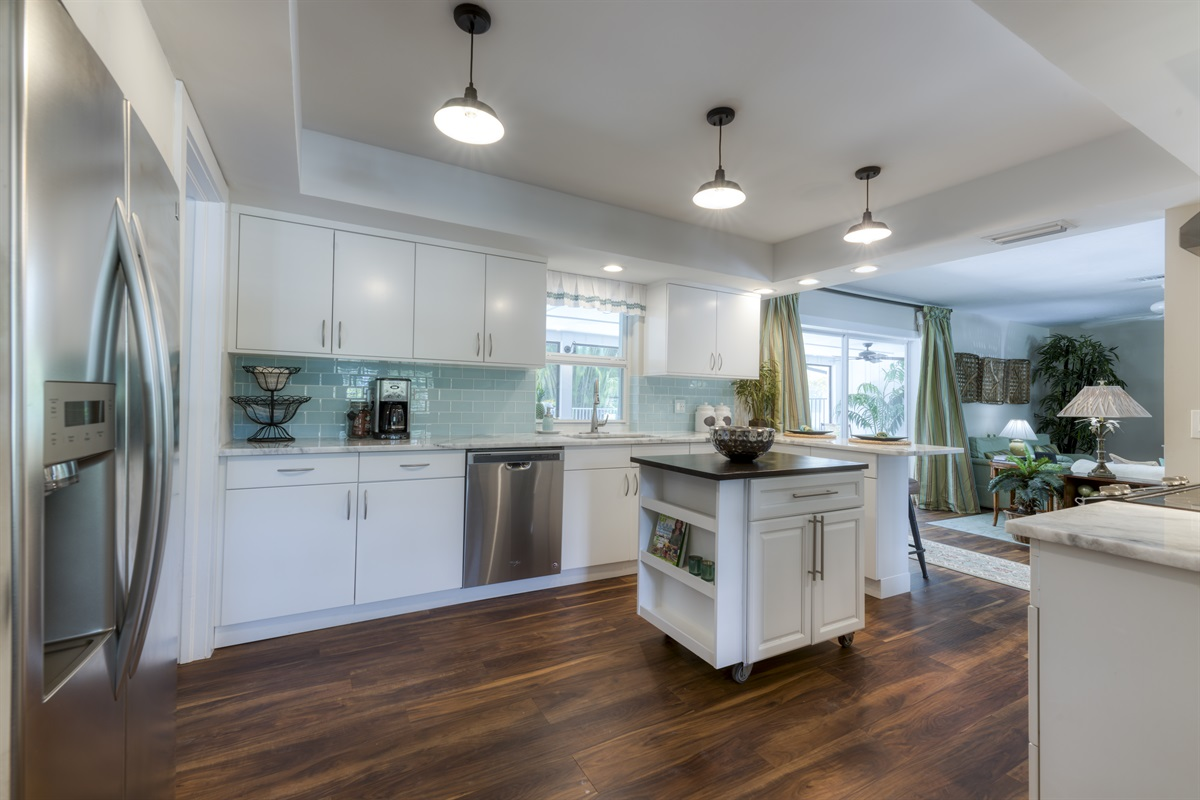 Step inside the open-plan magnificent kitchen with aqua tiled backsplash, stainless steel applicances, touchless purified system faucet and white and grey swirled marble counter tops. Bar counter space or two and granite top island for the Chef.