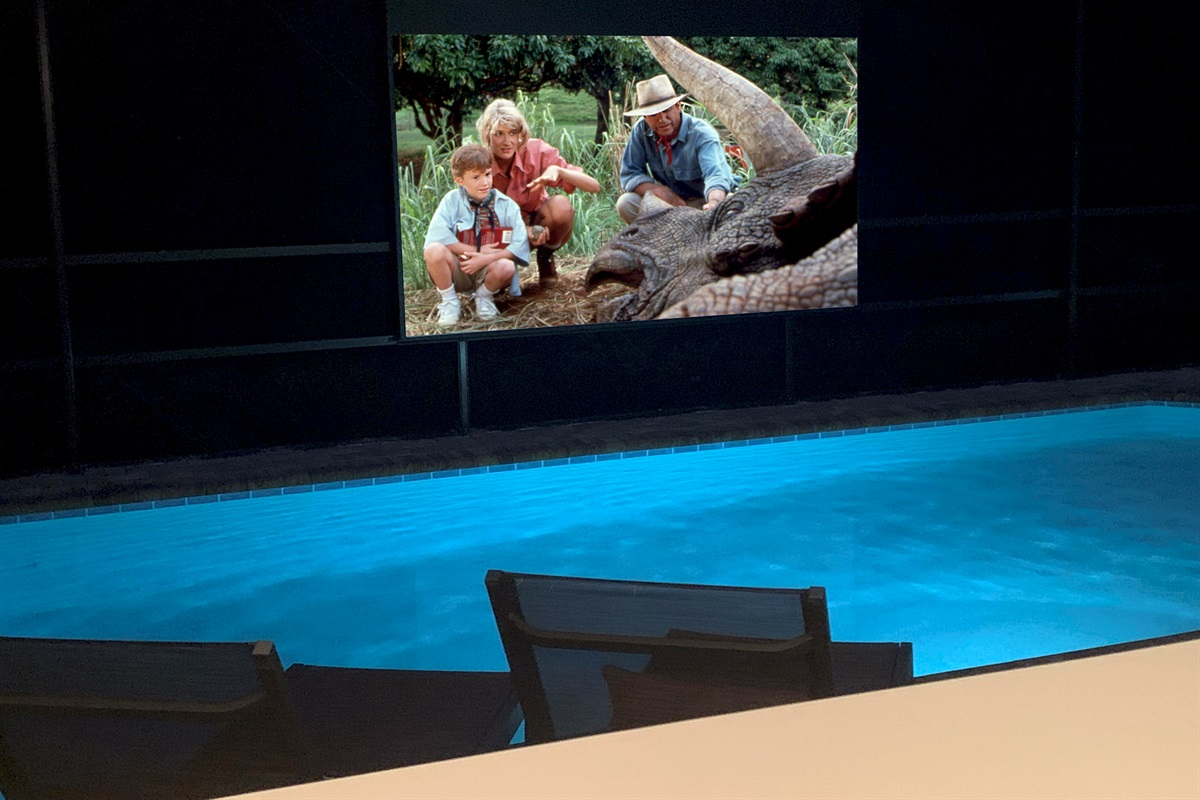 """Enjoy Movies Poolside On This 125"""" Screen With 4K Projector And Surround Sound"""