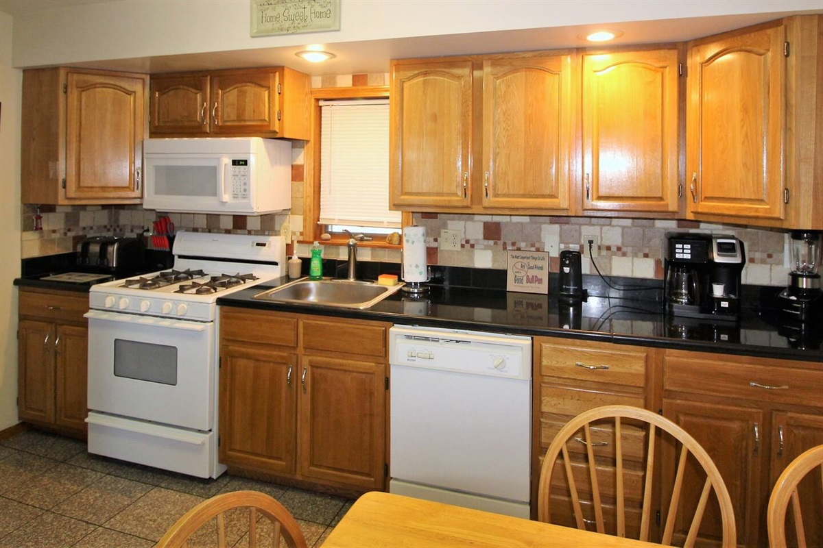 The fully appointed kitchen features granite countertops and flooring, along with a combo K-cup coffee maker, blender, toaster and can opener, along with other kitchen essentials