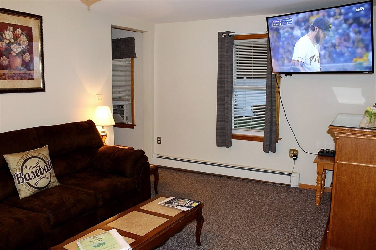 Living room with large flat screen smart TV with Roku.  Just bring your favorite streaming app and cheer on your favorite team.