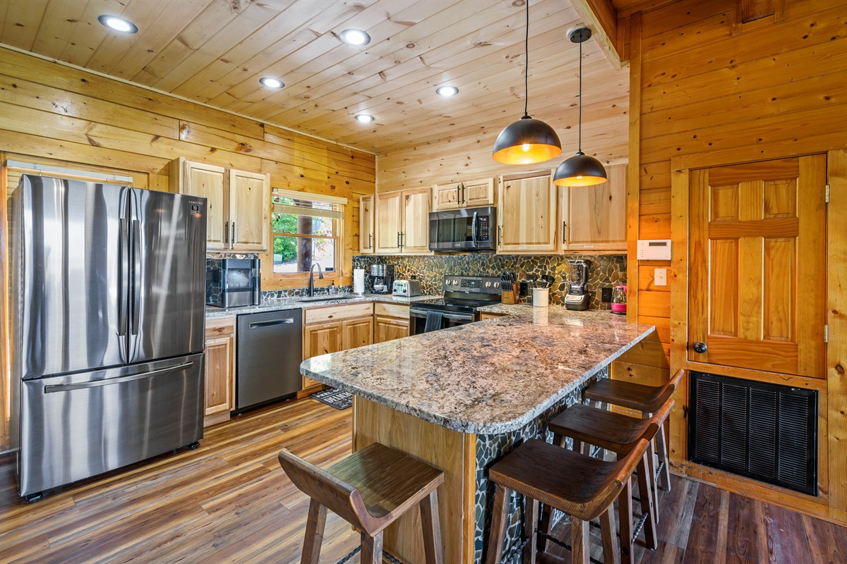Upgraded open Kitchen with brand new slate appliances, nugget ice machine, coffee maker, toaster and seating at the bar for 4
