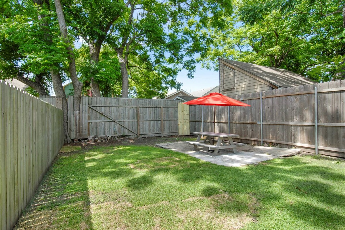 Backyard shared with neighboring guests.  Seating and charcoal grill.