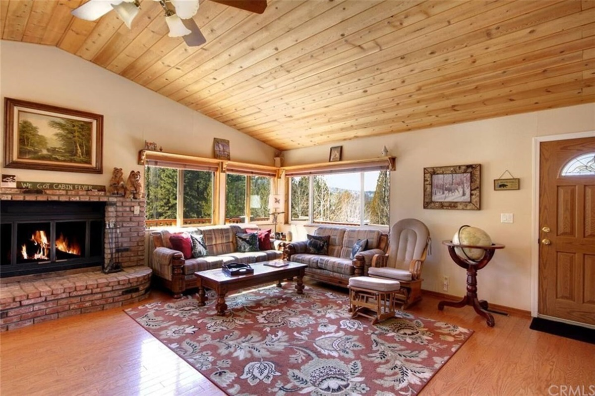 Living Room: Upstairs open-concept living room with cozy seating for 7 people, TV, game closet with extra folding chairs, wood burning fireplace, & access to wraparound deck.