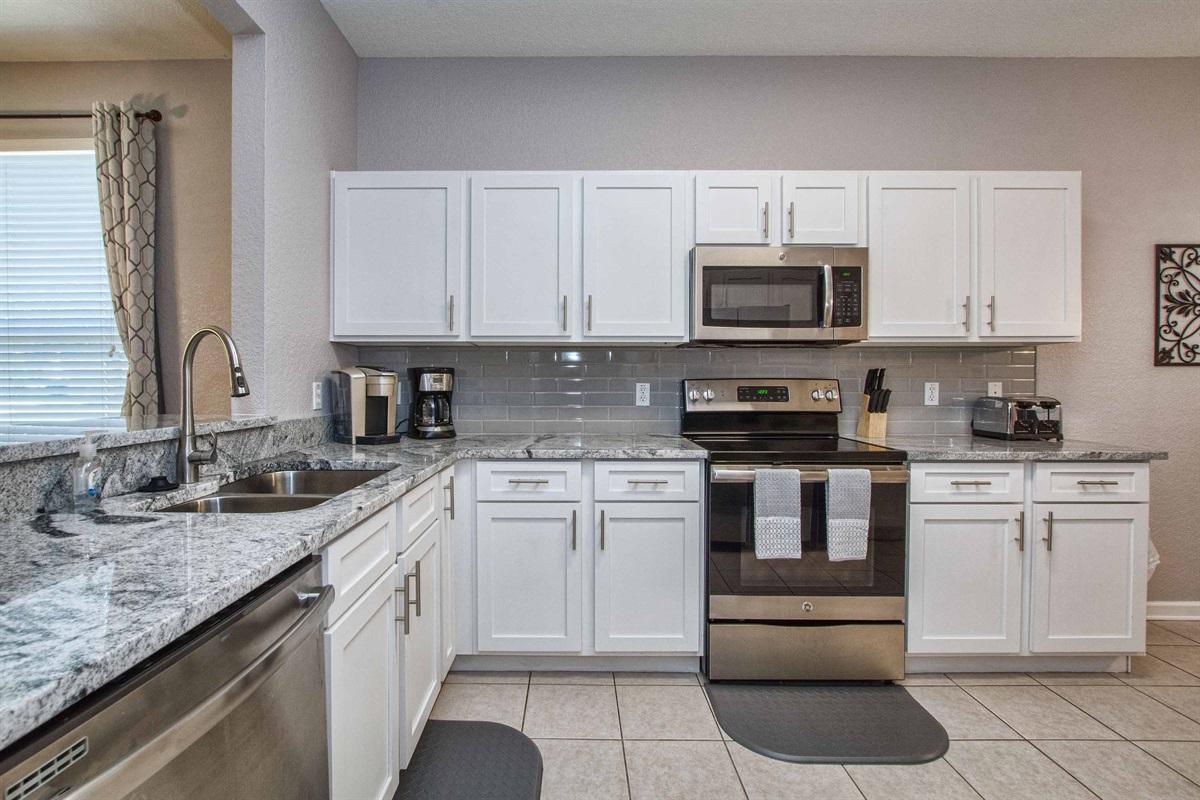Kitchen with granite countertops and Keurig machine.