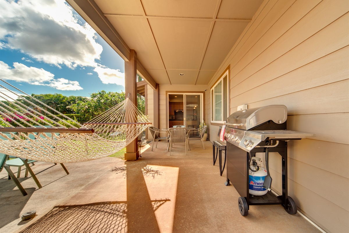 Open the kitchen doors to access the back patio which features a brand new gas grill, hammock, dining table, and outdoor games.