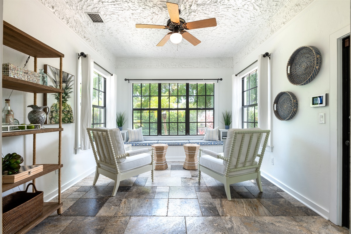 One of our favorite rooms! The inviting sunshine lit Den with large windows, lovely seating to play chess or games and beautifully decorated side bar with pineapple decor.