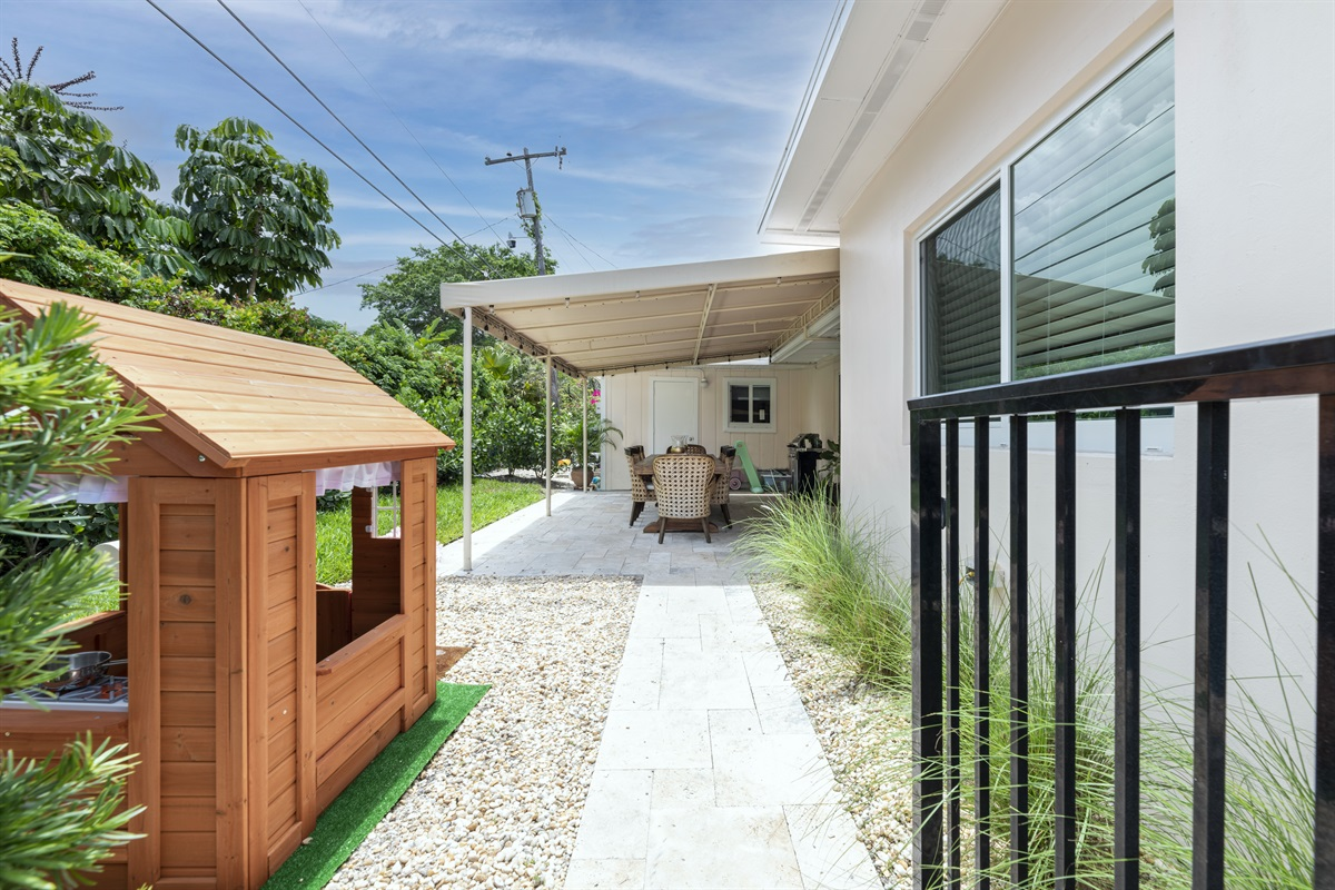 Cute back yard with kids playhouse and fenced in pool.