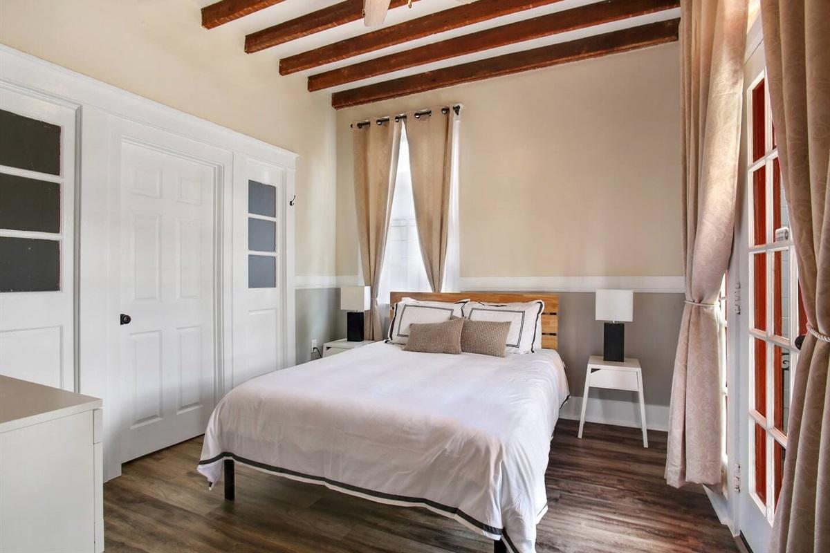 Bedroom 5. 1 queen bed, dresser, blackout curtains, connecting door to bedroom 4.